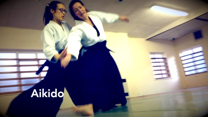 Photo of two students, Mari and Carole, practicing Aikido
